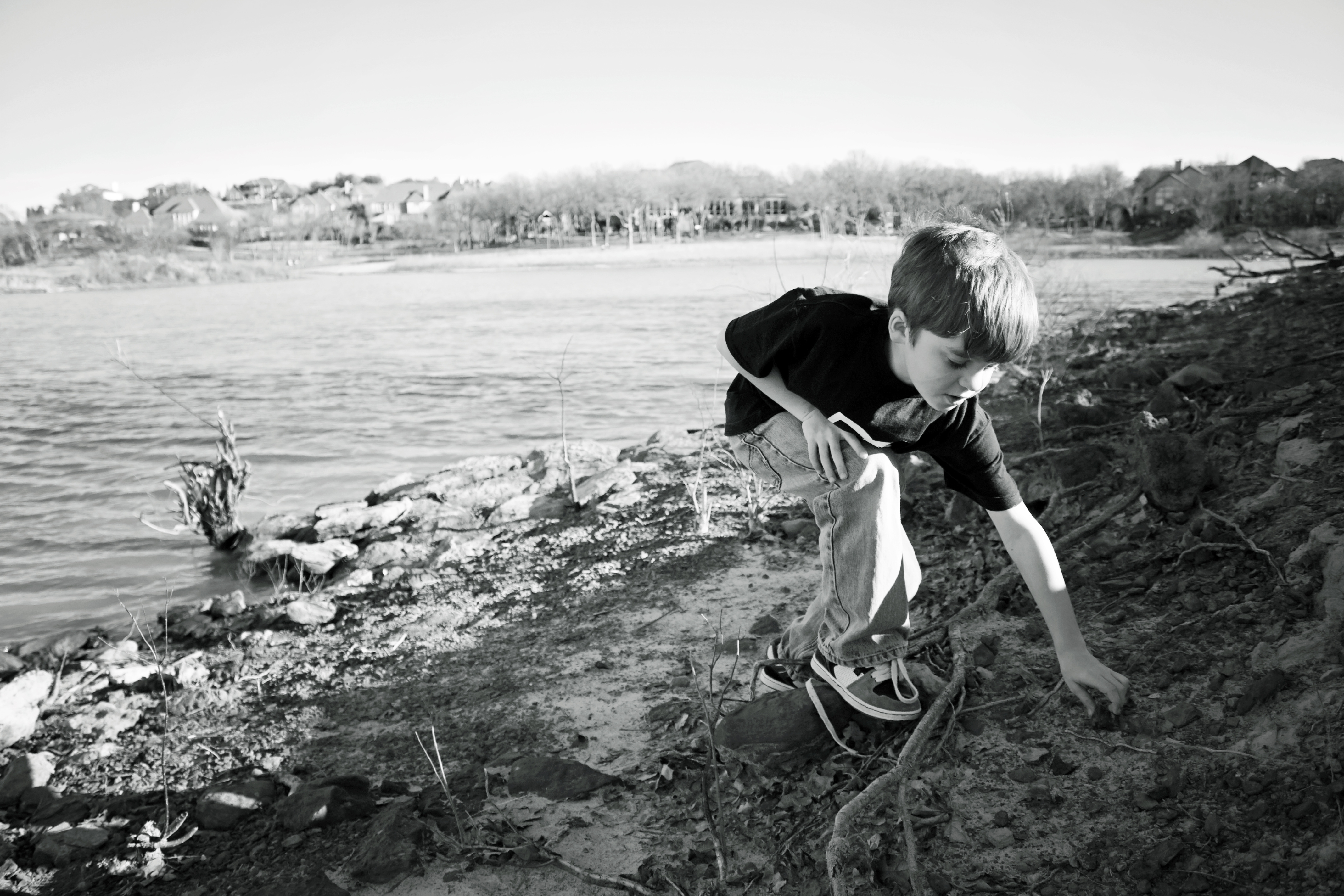 Boy playing in dirt by the lake